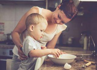 Uśmiechnięta mama gotuje z dzieckiem w kuchni