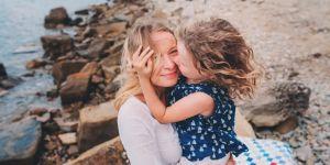 Uśmiechnięta mama przytula na plaży córeczkę
