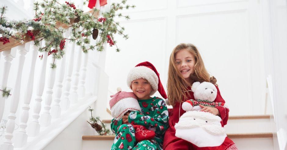 uśmiechnięte dzieci siedzą na schodach przed Świętami
