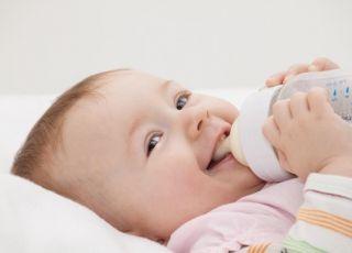 Uśmiechnięte niemowlę pije mleko z butelki