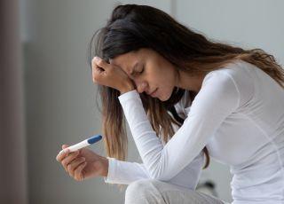 załamana kobieta z negatywnym testem ciążowym