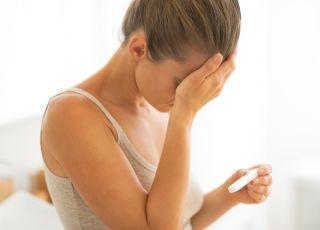 Załamana kobieta z powodu negatywnego testu ciążowego