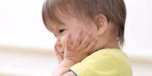 Zaskoczone dziecko trzyma rączki na buzi