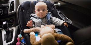 Zdziwione niemowlę siedzi w samochodzie w foteliku