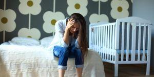 Zmęczona młoda mama siedzi na łóżku